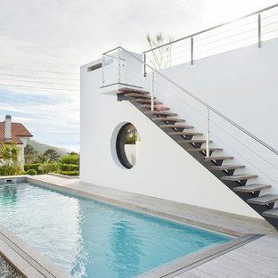 Idee per una grande piscina monocorsia minimalista rettangolare nel cortile laterale con pedane