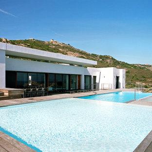 Exemple d'une grand piscine sur une terrasse en bois arrière tendance sur mesure.