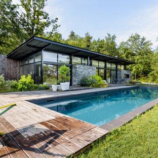 Foto di una grande piscina monocorsia design rettangolare davanti casa con pedane