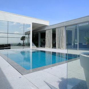 Ispirazione per una grande piscina a sfioro infinito contemporanea rettangolare sul tetto con pavimentazioni in pietra naturale