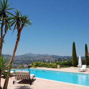 Exemple d'une très grande piscine arrière méditerranéenne rectangle avec du carrelage.