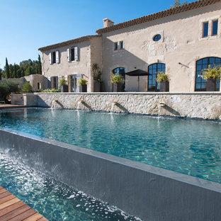 Aménagement d'une grand piscine sur une terrasse en bois à débordement campagne rectangle avec un point d'eau.