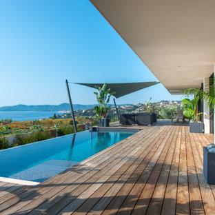 Immagine di una piscina a sfioro infinito minimal rettangolare con pedane