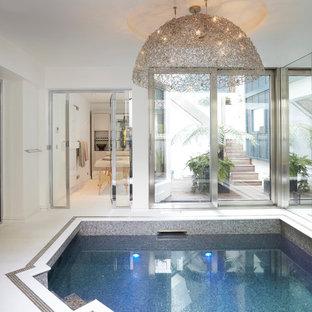 Réalisation d'une piscine intérieure design sur mesure avec du carrelage.
