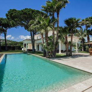 Exemple d'une grande piscine arrière exotique rectangle avec du carrelage.