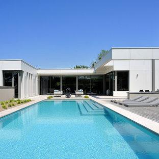 Aménagement d'une grand piscine sur une terrasse en bois arrière moderne rectangle.