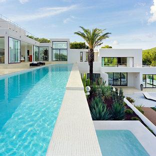 Exempel på en stor exotisk rektangulär pool på baksidan av huset, med kakelplattor