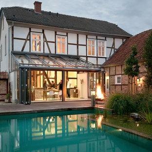 Exempel på en mellanstor lantlig rektangulär baddamm på baksidan av huset, med en fontän och trädäck