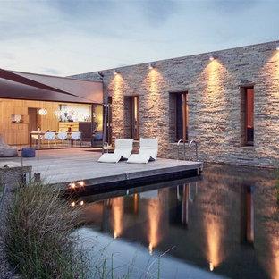 Inspiration för stora moderna anpassad baddammar, med trädäck