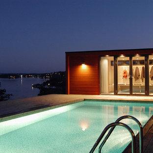 Inredning av en modern mellanstor rektangulär pool på baksidan av huset, med poolhus och trädäck