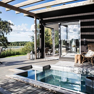 Design ideas for a mid-sized scandinavian side yard custom-shaped pool in Stockholm with a hot tub and decking.