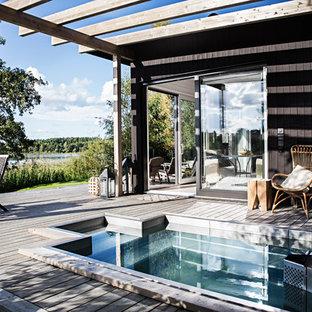 Imagen de piscina natural, nórdica, de tamaño medio, en patio lateral, con entablado