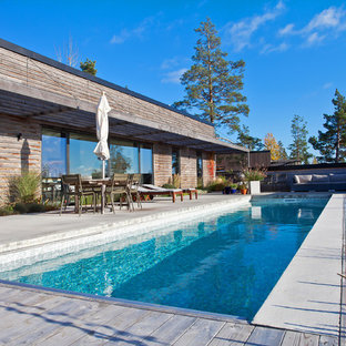 Diseño de piscina alargada, escandinava, grande, rectangular, en patio delantero, con losas de hormigón