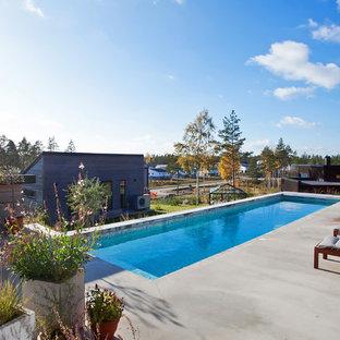 Foto de piscina escandinava, grande, rectangular, en patio delantero, con losas de hormigón