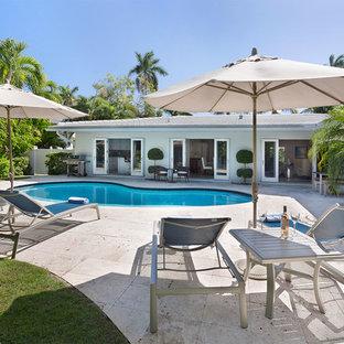 Ejemplo de piscina natural, contemporánea, de tamaño medio, tipo riñón, en patio trasero, con suelo de hormigón estampado