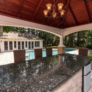Foto di una grande piscina chic personalizzata dietro casa con una dépendance a bordo piscina e pavimentazioni in pietra naturale