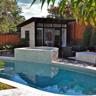 Modelo de piscinas y jacuzzis actuales, tipo riñón, en patio trasero, con suelo de baldosas