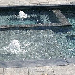 Imagen de piscina con fuente grande, rectangular, en patio trasero, con adoquines de ladrillo