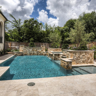Example of a large tuscan backyard stone and rectangular lap pool fountain design in Houston