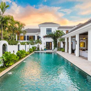Foto de piscina alargada, exótica, rectangular, en patio trasero, con suelo de baldosas