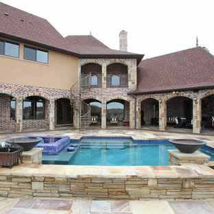 Example of a huge eclectic backyard stone and custom-shaped hot tub design in Dallas
