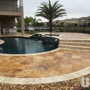 Foto de piscina elevada, grande, tipo riñón, en patio trasero, con adoquines de piedra natural