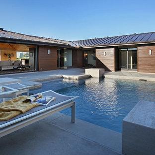 Ejemplo de piscina con fuente minimalista, de tamaño medio, a medida, en patio, con losas de hormigón