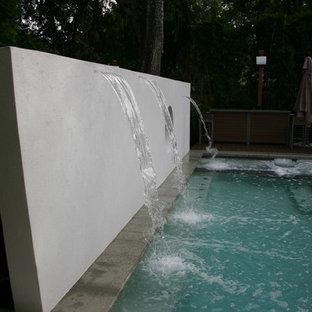 Foto di una grande piscina minimalista rettangolare dietro casa con fontane e pedane