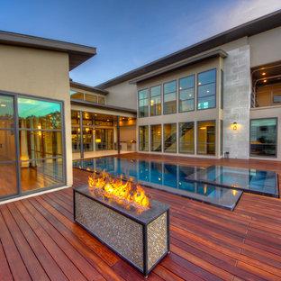 Aménagement d'une piscine sur une terrasse en bois à débordement contemporaine avec une cour.