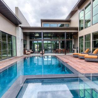 Ispirazione per una piscina a sfioro infinito contemporanea rettangolare in cortile con pedane e una vasca idromassaggio