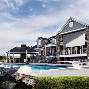 Foto di una grande piscina monocorsia stile americano rettangolare dietro casa con un acquascivolo e lastre di cemento