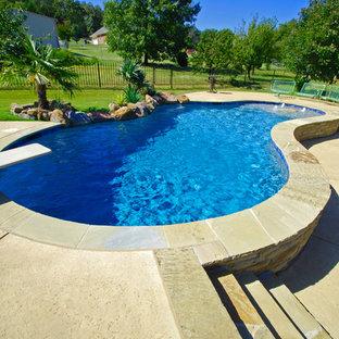 Foto de piscina campestre, de tamaño medio, tipo riñón, en patio trasero, con suelo de hormigón estampado