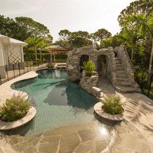 Ispirazione per una piscina stile americano personalizzata di medie dimensioni e dietro casa con un acquascivolo e pavimentazioni in pietra naturale