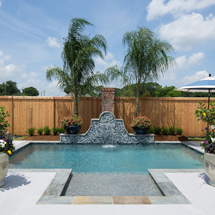 Inspiration for a small tropical backyard rectangular pool in New Orleans with a water feature and concrete slab.