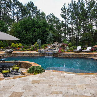 Inspiration for a large traditional backyard custom-shaped natural pool in Atlanta with a water feature and natural stone pavers.