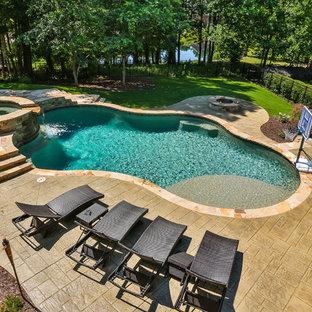 Ejemplo de piscina con fuente natural, exótica, grande, a medida, en patio trasero, con suelo de hormigón estampado
