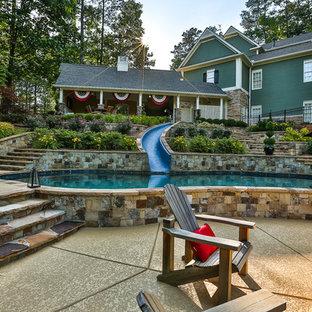 Esempio di una piscina stile americano personalizzata di medie dimensioni e dietro casa con un acquascivolo e pedane