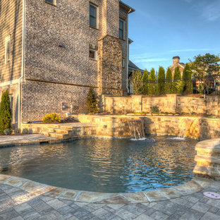 Large victorian backyard custom-shaped natural pool in Atlanta with a water feature and decking.