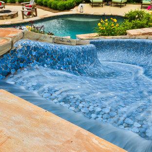 Foto de piscina con tobogán natural, tradicional, de tamaño medio, a medida, en patio trasero, con entablado
