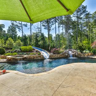 Foto de piscina con tobogán natural, exótica, grande, a medida, en patio trasero, con entablado