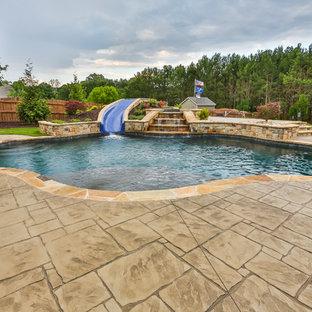 Modelo de piscina con tobogán natural, clásica, de tamaño medio, a medida, en patio trasero, con suelo de hormigón estampado