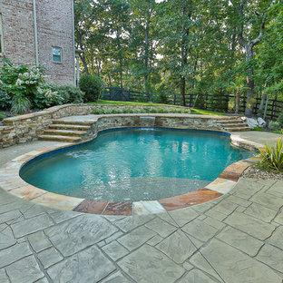 Foto de piscina con tobogán natural, contemporánea, de tamaño medio, a medida, en patio trasero, con suelo de hormigón estampado