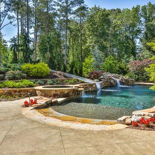 Ejemplo de piscina con tobogán natural, tropical, grande, a medida, en patio trasero, con suelo de hormigón estampado