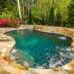 Design ideas for a large traditional backyard custom-shaped natural pool in Atlanta with brick pavers and a water feature.