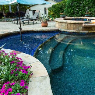 Idéer för en stor exotisk baddamm på baksidan av huset, med stämplad betong och spabad