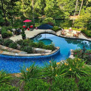 Ispirazione per una piscina naturale minimal personalizzata di medie dimensioni e dietro casa con un acquascivolo e pedane