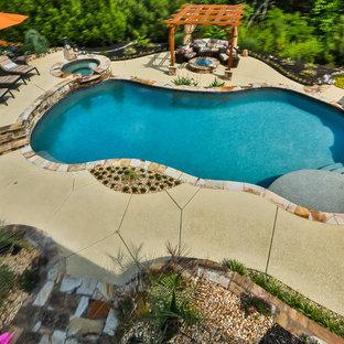 Ejemplo de piscina con fuente natural, clásica, grande, a medida, en patio trasero, con losas de hormigón