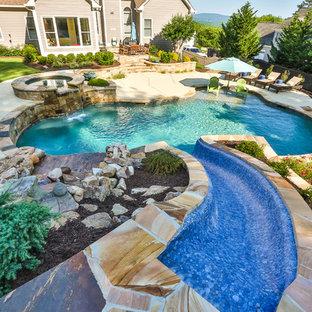 Modelo de piscina con tobogán natural, tradicional, grande, a medida, en patio trasero, con losas de hormigón
