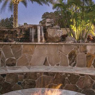 Foto de piscinas y jacuzzis naturales, tropicales, extra grandes, tipo riñón, en patio trasero, con adoquines de piedra natural