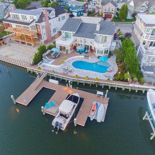 Diseño de piscina natural, costera, grande, tipo riñón, en patio trasero, con suelo de baldosas